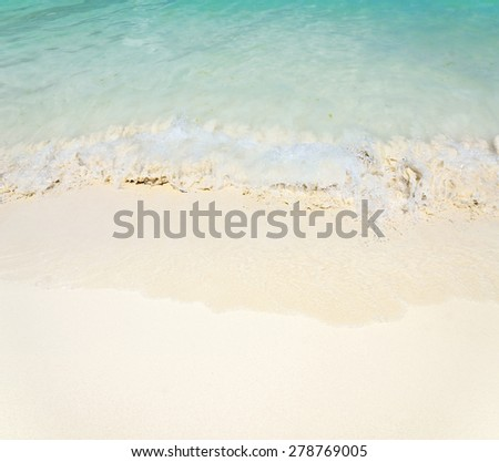 Waves on a sandy beach comes to shore - stock photo