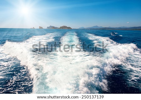 Waves on blue sea behind the speed boat water with bright sun shining on the sky - stock photo
