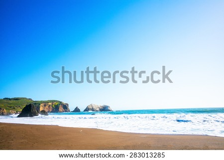 Waves on Rodeo Beach Cove in the Marin Headlands, just north of San Francisco, California, USA.  Blue sky on a sunny day. - stock photo