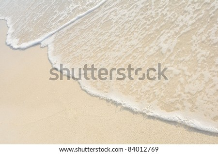 Waves on Shore of Tropical White Sand Beach on a Sunny Day - stock photo