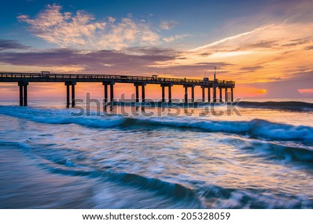 Waves on the Atlantic Ocean and fishing pier at sunrise, St. Augustine Beach, Florida. - stock photo