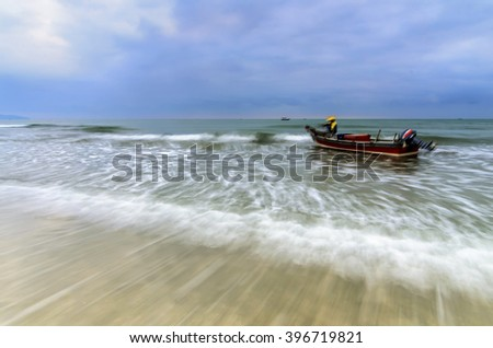 Waves on the beach, soft focus due to long exposure. Blue sky with copy space available.