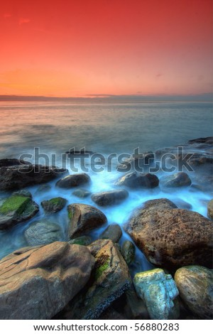 Waves on the rocks at sunset in France - stock photo