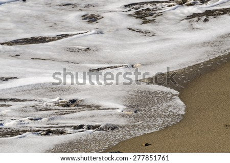 waves on the sand of the shore - stock photo
