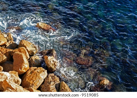 Waves pounding against the coastal rocks by shore of the Mediterranean sea in Monaco. - stock photo