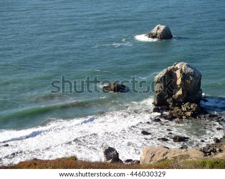 Waves roll toward large rocks and shore on the coast of Marin in California. - stock photo