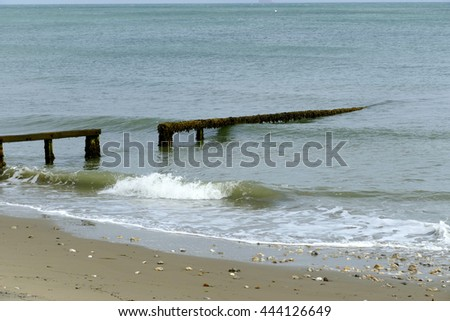 Waves rolling onto the beach through a groyne wave breaker.