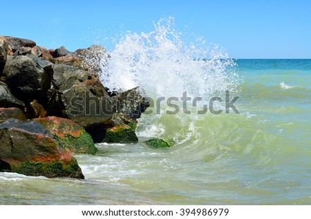 Waves splash on the large boulders on the beach