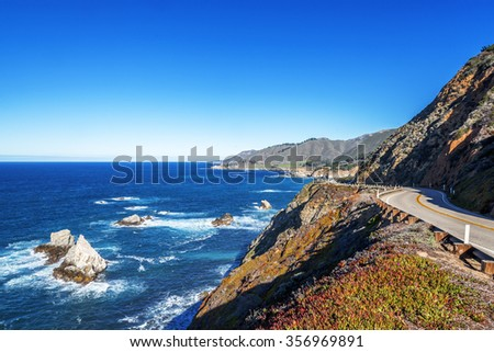 Waves splashing on huge rocks, off shore, along a rocky coastline, blue sky covered mountain tops, aquamarine waters, traveling the Big Sur Highway (Highway 1), on the California Central Coast. - stock photo