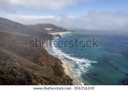 Waves splashing on huge rocks, off shore, along a rocky coastline, fog & cloud covered mountain tops, bixby bridge, traveling the Big Sur Highway (Highway 1), on the California Central Coast.  - stock photo