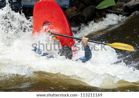Waves swamp a competitor in the kayak competition. - stock photo