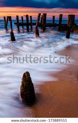 Waves swirl around pier pilings in the Delaware Bay at sunset, seen from Sunset Beach, Cape May, New Jersey. - stock photo
