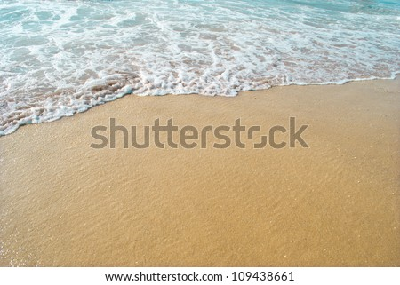 Waves wash over golden sand - stock photo