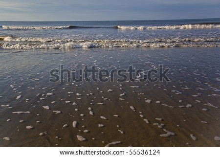 Waves washing ashore shortly after sunrise - stock photo