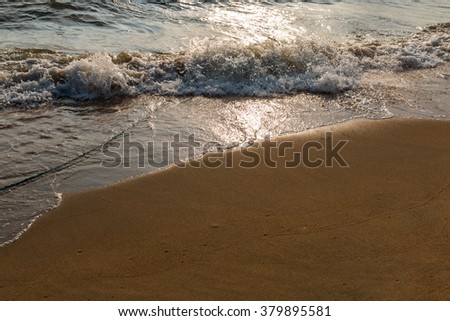 Waves washing the sand with the sun.
