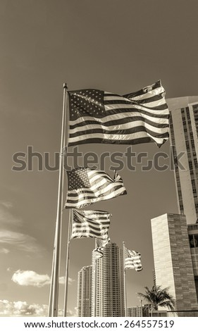 Waving american flags against modern buildings and blue sky. - stock photo