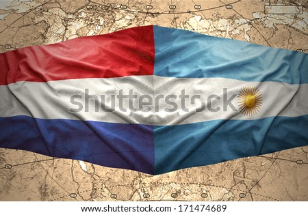 Waving Argentinean and Dutch flags on the background of the political map of the world - stock photo