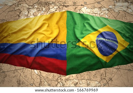 Waving Brazilian and Colombian flags on the background of the political map of the world - stock photo