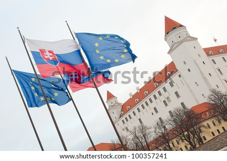 waving European union and Slovak republic flags in front of Bratislava Castle. - stock photo