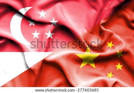 Waving flag of China and Singapore - stock photo