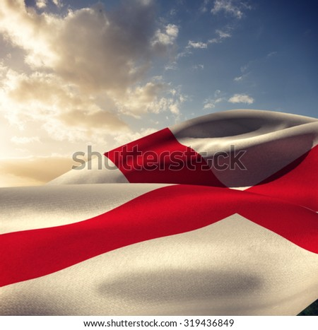 Waving flag of England against blue sky with clouds