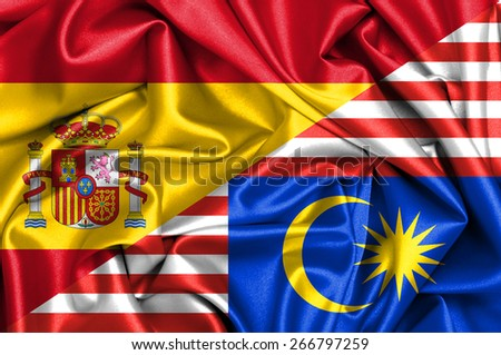 Waving flag of Malaysia and Spain - stock photo