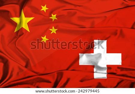 Waving flag of Switzerland and China - stock photo