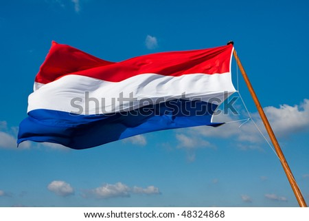 Waving flag of The Netherlands on the flagpole against blue sky with some clouds