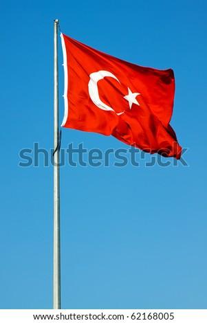 Waving flag of Turkey under sunny blue sky - stock photo