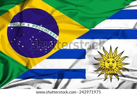 Waving flag of Uruguay and Brazil - stock photo