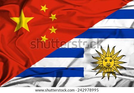 Waving flag of Uruguay and China - stock photo