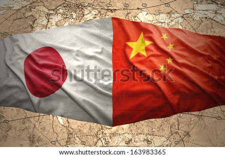 Waving Japanese and Chinese flags on the background of the political map of the world - stock photo