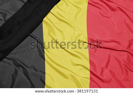 waving national flag of belgium with black mourning ribbon  - stock photo