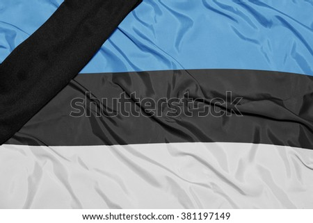 waving national flag of estonia with black mourning ribbon  - stock photo