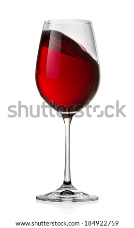 Waving red wine in a glass isolated on a white background - stock photo