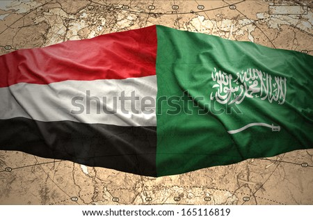 Waving Saudi Arabia and Yemeni flags on the background of the political map of the world