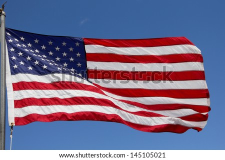Waving United States Flag Waving United States of America flag.  Beautiful waving flag with brilliant blue sky behind it.