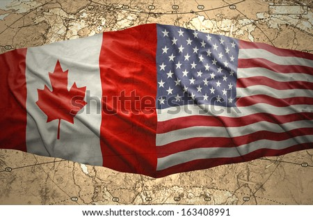 Waving United States of America and Canadian flags on the background of the political map of the world - stock photo