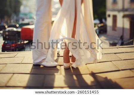 waving wedding dress,bride and legs of husband - stock photo