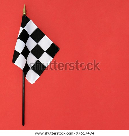 Wavy Black and White Finish Line Checkered Flag with flagpole isolated on red background with room for your text - stock photo