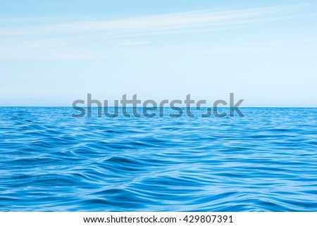 Wavy blue ocean with clouds in the blue sky