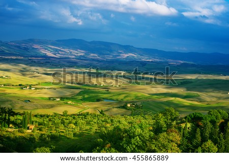 Wavy fields in Tuscany with shadows and farms, Italy. Natural outdoor seasonal spring background with blue sky and clouds. - stock photo