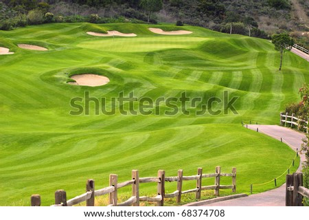 Wavy green golf field with a wooden fence - stock photo