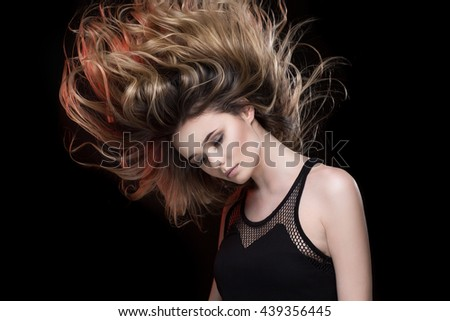 Wavy hair. Attractive sensual young female model posing with her gorgeous windswept long hair on black background with red lighting - stock photo