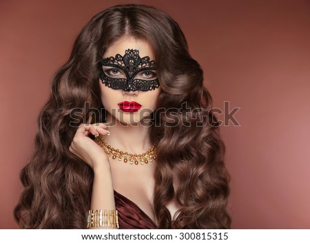 Wavy Hair. Beautiful Brunette Girl. Makeup. Red Lips. Fashion lady wearing venetian masquerade carnival mask. Jewelry. Beauty Model Woman. Healthy Long Curly Hairstyle. - stock photo