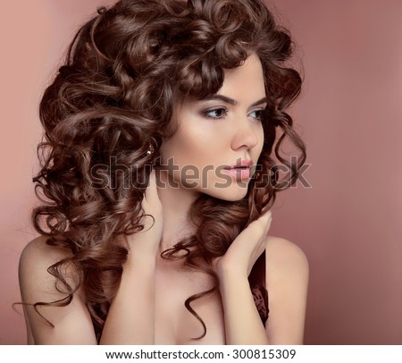 Wavy hair. Beautiful girl with makeup. Curly hairstyle. Brunette. Expressive eyes stare. Fashion young woman isolated on  studio beige background. Luxury vogue style - stock photo