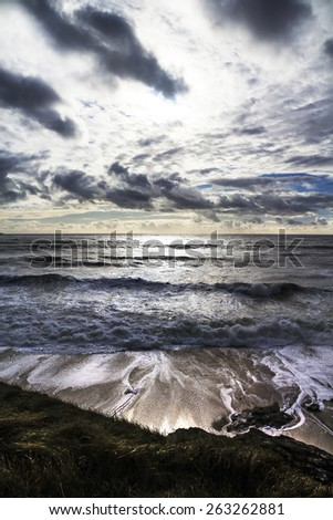 Wavy ocean with a white sun shining through the storm clouds, dramatic light  Bretagne,France - stock photo