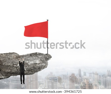 Wavy red flag on top of cliff with Businessman hanging mist city view background