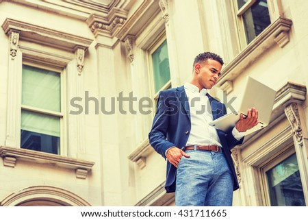Way to Success. African American college student studying in New York, wearing blue blazer, white shirt, standing outside vintage office building, working on laptop computer. Instagram filtered effect - stock photo