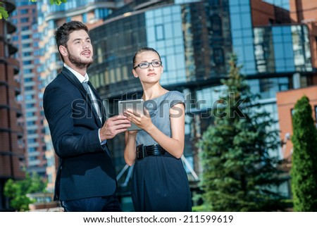 Way to success. Couple businessmen talking on the street and make the case for the tablet. Successful and confident businessman and businesswoman standing in front of office building and look forward - stock photo